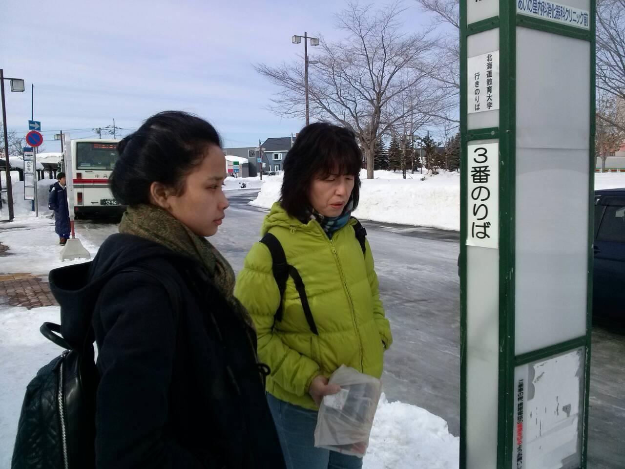 Sasa dan Suzuki-san sedang menunggu bus di halte depan stasiun